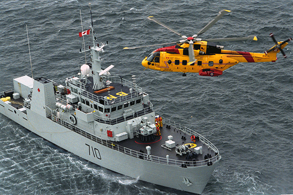 CX2003-0152-06c 442 Squadron's Cormorant CH-149 #502 prepares to raise a SAR tech from the deck of the HMCS Brandon, an Maritime Coastal Defence Vessel during a training exersize off of Esquilmalt Harbour, Vancouver Island, British Columbia.